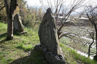 広い敷地に石を積まれた庚申がたくさんある