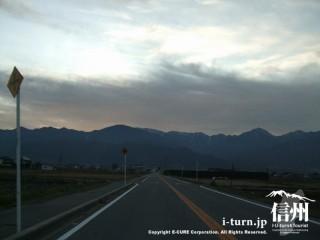 誰もいないまっすぐの道の先にはアルプスの山々の風景