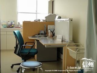 明るい部屋で医師の机と椅子、患者さんの椅子と持ち物籠が用意