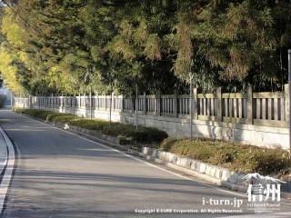 石塀が続いていて道路が平行して走っています