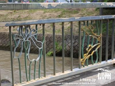 橋の欄干にアヤメとニジマス