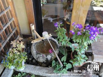 そば処さくら玄関の水鉢と生け花