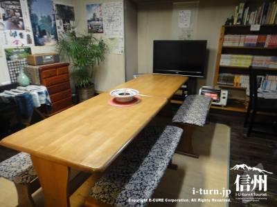 長いテーブルの奥にテレビ
