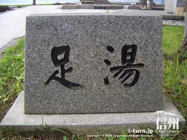 足湯の看板は石