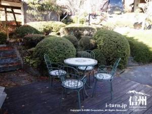 玄関横の屋外に丸いテーブルと椅子