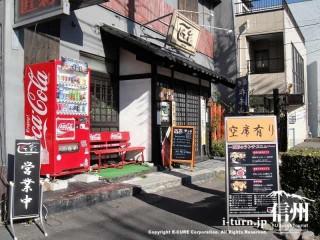 居酒屋風の入口、赤い自動販売機が設置、赤いイスも