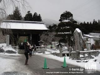 雪の積もった光前寺の入口の山門
