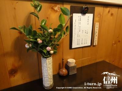 野麦のテーブル上の椿と七味、楊枝、おしながき