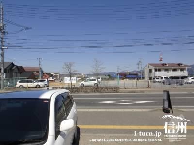 道路の反対に広い空き地の駐車場