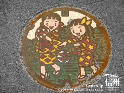 手まりで遊ぶ女の子二人が描かれたマンホール